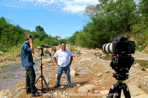 The Technical Director of Fundacion Natura, Huáscar Azurduy, explains the importance of protecting the limited water sources in Santa Cruz from getting contaminated by cattle feces. And guess who walks right into the shoot... (Photo credit: GLP films/IDRC).